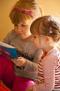 Two girls reading book portrait of cute young preschool together Stock Photo