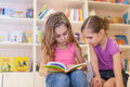 Two girls are reading an interesting book in the library Stock Images