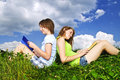 Two girls reading outdoors in summer books together outside on grass Royalty Free Stock Image