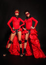 Two girls in red dresses on black background Royalty Free Stock Photos