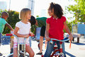 Two girls riding tricycles in playground looking at each other smiling Royalty Free Stock Photos