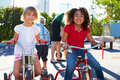 Two girls riding tricycles in playground smiling at camera Stock Photo