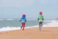 Two girls run a race on beach seaside Royalty Free Stock Photo