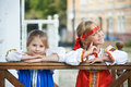 Two girls in russian national costumes on a house porch Stock Photos