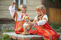Two girls in russian national costumes with samovar and bagels Stock Photos