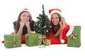 Two girls in santa hats with presents Royalty Free Stock Photo