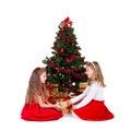 Two girls sit near Christmas tree.
