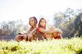 Two girls sitting back to back young women on grass Stock Image