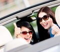 Two girls sitting in the car and thumbing up happy turn back have fun while having little trip Stock Photos