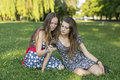 Two girls sitting on the grass and use a smartphone. Royalty Free Stock Photo