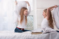 Two girls sitting pillow fight in bed. Royalty Free Stock Images