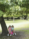 Two girls sitting on pink space hopper beneath tree in park smiling portrait Stock Photo