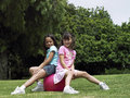 Two girls sitting on pink space hopper in park smiling side view portrait Royalty Free Stock Photography
