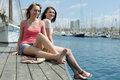 Two girls students enjoying sunny day on the sea berth and smiling Stock Image