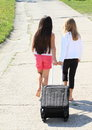 Two girls with suitcase barefoot walking black chech in baggage on beton road Stock Images