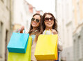 Two girls in sunglasses with shopping bags in ctiy sale happy people and tourism concept smiling Royalty Free Stock Images
