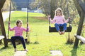 Two girls swinging on two swings smiling kids little playing and Royalty Free Stock Photography