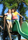 Two girls talking on slide kids standing and a Stock Photo