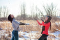 Two girls throwing snow and laughing female friends walking in park in winter Stock Photo