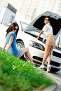 Two girls try to repair the broken car on the road pretty Stock Photo