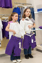 Two girls trying on the same dress in the store childrens clothes Royalty Free Stock Photos