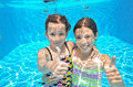 Two girls underwater in swimming pool happy active kids play diving and having fun children on summer vacation sport concept Royalty Free Stock Photos