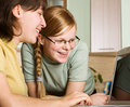 Two girls uses  home computer Royalty Free Stock Image