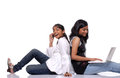 Two girls using laptop and mobile phone Royalty Free Stock Photo