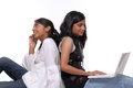 Two girls using laptop and mobile phone Royalty Free Stock Image