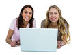 Two girls using a laptop and smiling Stock Images