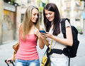 Two girls using smartphone navigating system Royalty Free Stock Photo