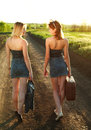 Two girls walking along the road at sunset looking each other in countryside Stock Images