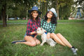 Two girls walking with his dog. cowboy hat and Royalty Free Stock Photo