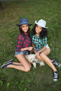 Two girls walking with his dog. cowboy hat and plaid shirt Royalty Free Stock Photo