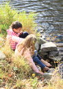 Two girls washing their feet young kids barefoot in water of river Stock Photos