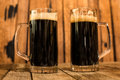 Two glass of fresh dark beer on wooden table Royalty Free Stock Photo