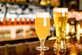A two Glass of light beer on a pub with bokeh background Royalty Free Stock Photo