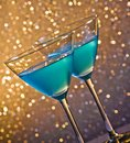 Two glasses of blue cocktail on table golden tint light bokeh background Royalty Free Stock Image