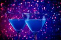 Two glasses of blue cocktail on table and violet tint light bokeh background Stock Photo