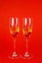 Two glasses with champagne and cherries on red Royalty Free Stock Photo
