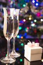 Two glasses of champagne nad gift on shiny background Royalty Free Stock Images