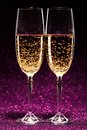 Two glasses of champagne ready for christmas celebration on purple background Stock Images