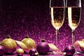 Two glasses of champagne ready for christmas celebration on purple background Royalty Free Stock Images
