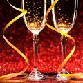 Two glasses of champagne ready for christmas celebration on red background Royalty Free Stock Images