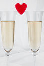 Two glasses with champagne and symbolic heart on a white background Stock Photos