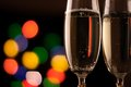 Two glasses of champagne toasting against bokeh lights background Stock Photo