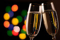 Two glasses of champagne toasting against bokeh lights background Stock Photography