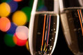 Two glasses of champagne toasting against bokeh lights background Royalty Free Stock Photo