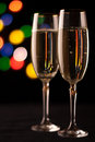 Two glasses of champagne toasting against bokeh lights background Royalty Free Stock Image