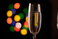 Two glasses of champagne toasting against bokeh lights background Royalty Free Stock Photography